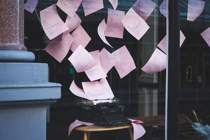 Pink papers flying from a typewriter